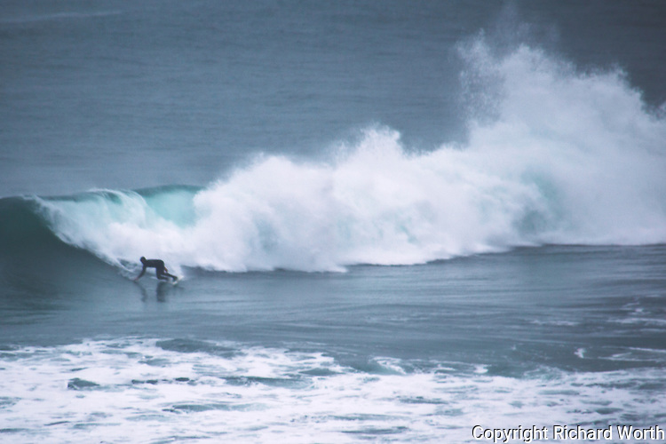 A surfer rides a wave at Montara State Beach on the first day of what should be a week of storm and after storm aimed at the Pacific Coast near San Francisco.