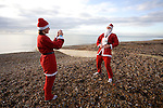 JAMES BOARDMAN / 07967642437.A competetor takes a photo of her friend before the Brighton's 2.5k Santa Dash on the seafront December 12, 2009.
