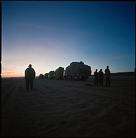 Sahara desert, Libya-Chad, November/December 2004..Every week, a convoy of 40 privately owned Libyan trucks loaded by the WFP with about 1000 metric tons of western food aid cross 2500 km of deep desert across Libya and Chad to reach more than 200 000 refugees from Darfur in camps near the Sudanese border. Night prayer.