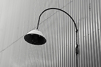 Electric light fixture on wall of a corrugated metal building, Granville Island, Vancouver, BC, Canada