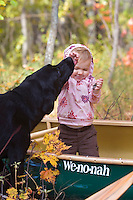 A young girl gets a kiss from a black labrador dog while playing in a green canoe on a fall day near Marquette Michigan.