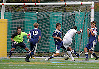 HYATTSVILLE, MD - OCTOBER 26, 2012:  Arion Sobers-Assue (13) of DeMatha Catholic High School blasts a shot between Nelson Reed (11) and Camyer Matini (5) of St. Albans during a match at Heurich Field in Hyattsville, MD. on October 26. DeMatha won 2-0.