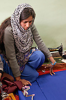 Dehradun,  India.  Indian Muslim woman studying cloth before measuring and cutting.