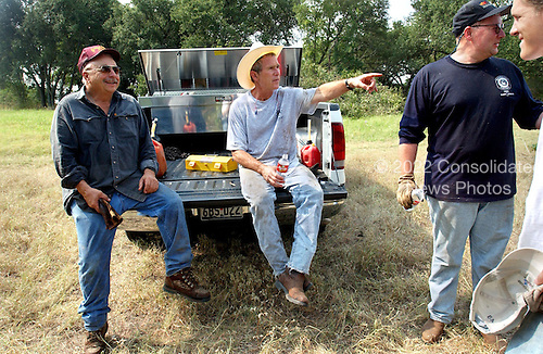 United States President George W. Bush takes a break from cedar clearing at his ranch in Crawford, Texas, Friday, August 9, 2002. Also pictured are, from left, friend Ken Englebrecht, Deputy Chief of Staff Joe Hagin and White House staffer Reed Dickens. <br /> Mandatory Credit: Eric Draper - White House via CNP