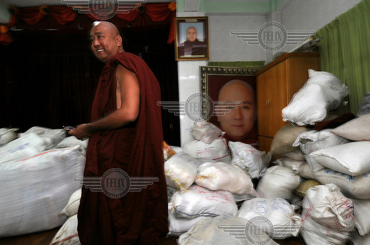 Dr. Ashin Kovida, from a leading monastery in Yangon (Rangoon), stands in front of goods that will shortly be driven out to victims of Cyclone Nargis in the delta area. They bought most items with money donated from members of the Myanmar public. Cyclone Nargis hit Burma on 02/05/2008.