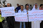 Palestinian employees hold placards during a protest against not receiving their salaries, in Gaza City on July 01, 2014. Many issues involving the Strip, such as the fate of former employees of the Hamas government, have yet to be addressed by the new unity government. Photo by Mohammed Asad
