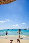 Peope enjoying the beach on Mykonos Island in Greece