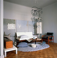 A simply furnished living room with varying tones of grey. The furniture has a retro feel and an unusual metal pendant light hangs from the ceiling