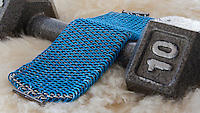 "A blue and silver dragonscale weave maille bracelet.  It's made from saw cut 18 gauge 1/4"" ID blue anodized aluminum rings and saw cut 19 gauge 5/32"" ID bright aluminum rings.  The clasp is a gunmental plated slide clasp.  The bracelet is on a sheepskin rug and a 10 pound dumbbell.   Handmade by Michelle."