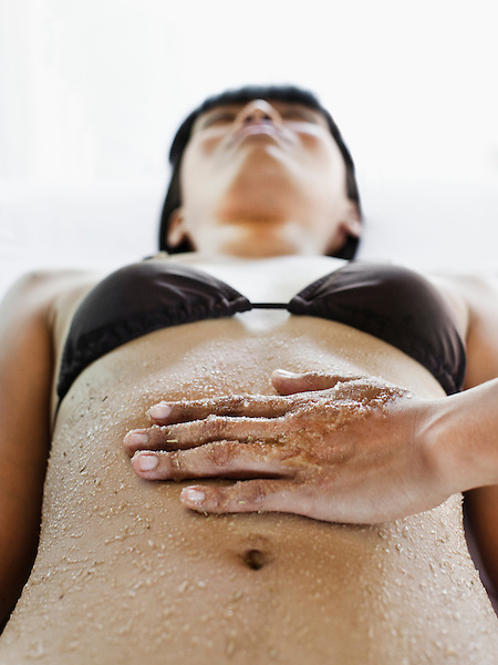Young Asian woman receiving body scrub at Kayumanis Spa, Kayumanis Ubud, Bali, Indonesia. A therapist plays chimes to signal the beginning of this treatment; the scrub is made with tea tree oil (an antiseptic), sea salt (to exfoliate dead skin), and honey (to nourish skin)
