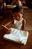 Children studying in school, writing in notebook, in Yap, Micronesia.