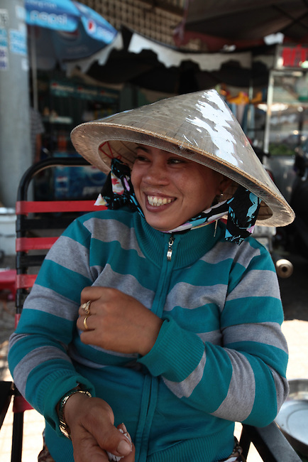 A street vendor grins as her photograph is taken in District 11 in Ho Chi Minh City, Vietnam.  Aug. 16, 2011.