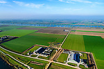 Nederland, Brabant, Gemeente Waspik, 28-10-2014; Overdiepsche polder: in het kader van het programma 'Ruimte voor de Rivier' (bescherming tegen hoogwater door rivierverruiming), is de dijk langs de Bergsche Maas (boven in beeld) verlaagd. Bij hoogwater kan de Overdiepse polder overstromen. De boerderijen in de polder zijn gesloopt en verplaatst naar de dijk van het Oude Maasje. De nieuwe boerderijen met bijgebouwen staan op terpen.<br /> Depoldering of Overdiep Polder, farms are relocated and built on mounds. This makes it possible for the river to overflow the polder in case of heigh waters.<br /> luchtfoto (toeslag op standard tarieven);<br /> aerial photo (additional fee required);<br /> copyright foto/photo Siebe Swart