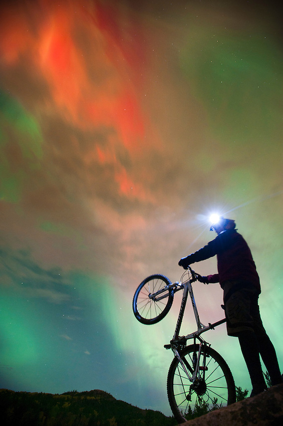 Night mountain bike riding with aurora borealis northern lights near Marquette Michigan.