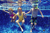 Two girls and boy with diving mask playing and swimming under water in a pool