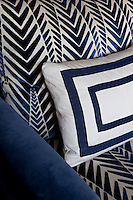 Detail of a blue and white patterned armchair and cushion