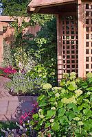 Garden gazebo building with hydrangeas, garden path and privacy wall, home landscape
