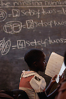 A students studies in the church sanctuary at the Sharing and Caring Center in Kamwokya, Kampala, Uganda March 22, 2004. The Catholic church serves as a classroom for students who have lost parents to HIV/AIDS and cannot affort public school. The program also accepts the very poor who have parents but who still cannot afford the public system. (Rick D'Elia)<br />
