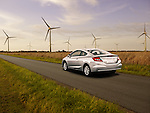 One 2012 Honda Civic Coupe EX driving on country road near windmills.