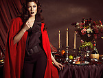 High fashion photo of a beautiful woman in red coat standing at a table with remains of a festive dinner