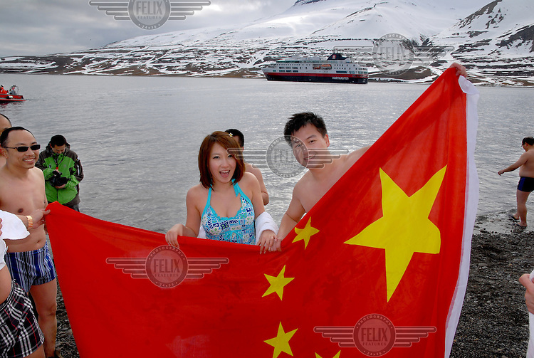 photograph by XAVIER CERVERA 06/2010.A chinese couple from China on their honey moon, in Skansenbukta, a stony beach with beautiful cliffs in Billfjorden, after a 1,7 degrees water temperature swim bath; close to Longyearbyen capital, Spitsbergen island, Svalbard archipielago; in a afternoon landing to the beach from MS Fram, a norwegian vessel