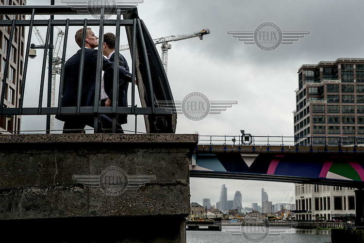 Office workers in Canary Wharf with the City of London tower blocks in the distance.
