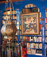 Curved and painted bookshelves and a Moroccan lantern create an exotic touch in the mezzanine library