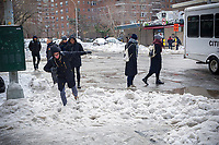 Pedestrians attempt to maneuver tiny pathways in the snow without falling into the banks of frozen snow at crossings in the Chelsea neighborhood of New York on Wednesday, March 15, 2017 after Winter Storm Stella deposited 7.2 inches in Central Park.  (© Richard B. Levine)