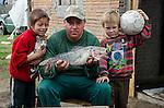 Colônia de pescadores Z24 - Lagoa Mirim. Comunidade Santa Isabel, no município de Arroio Grande no Rio Grande do Sul. O pescador Josué mostra o jundiá que pescou, junto com seus filhos que o ajudam a pegar larvas (capitão), que são usadas como iscas.