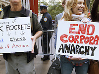 USA. New York City. Occupy Wall Street (OWS) is a people-powered movement that began on September 17, 2011 in Liberty Square in the Wall Street financial district of Manhattan. The protesters have created a small campsite at the Zuccotti Park site. OWS and has spread to over 100 cities in the United States and actions in over 1,500 cities globally. OWS is mainly protesting social and economic inequality, corporate greed, corruption and influence over government&mdash;particularly from the financial services sector&mdash;and lobbyists.  It is fighting back against the corrosive power of major banks and multinational corporations over the democratic process, and the role of Wall Street in creating an economic collapse that has caused the greatest recession in generations. The protesters' slogan, &quot;We are the 99%&quot;, refers to the difference in wealth and income growth in the U.S. between the wealthiest 1% and the rest of the population. OWS aims to expose how the richest 1% of people are writing the rules of an unfair global economy that is foreclosing on our future. OWS has being organized using a non-binding consensus based collective decision making tool known as a &quot;people's assembly&quot;. Police and protestor with placard: Spank the banks. 22.10.2011 &copy; 2011 Didier Ruef