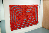 Underfloor heating rig displayed on a wall in the Renewables section at the Able Skills Training Centre, Dartford, Kent.