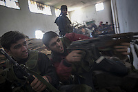 In this Saturday, Dec. 15, 2012 photo, a Syrian rebel fighter aims toward government forces during heavy clashes inside one militar academy besieged by rebels at the north of Aleppo, Syria. The Free Syrian Army took control over the Academy after several hours battling the troops loyal to President Bashar al-Assad. Among the casualities are one FSA General and one Syrian journalist. (AP Photo/Narciso Contreras)