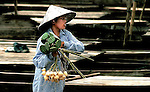 A woman rushing to an arriving ferry to sell her lotus seeds and tubers to the passengers in Pakse, Laos.