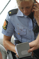 (Oslo July 22, 2011)A blood stained police woman takes notes. A large vehicle bomb was detonated near the offices of Norwegian Prime Minister Jens Stoltenberg on 22 July 2011. Although Stoltenberg was reportedly unharmed the blast resulted in several injuries and deaths. <br />