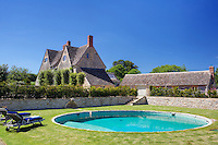 A circular swimming pool is situated in the middle of the sunken garden enclosed by a stone wall