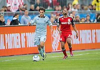 Sporting KC midfielder/forward Graham Zusi #8 and Toronto FC forward Javier Martina #33 in action during an MLS game between Sporting Kansas City and the Toronto FC at BMO Field in Toronto on June 4, 2011..The game ended in a 0-0 draw...