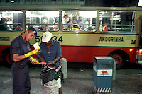 A Guardia Municipal officer checks the ID of a suspicious passer-by in front of the operation's bus. He was allowed to go on his way after an extensive look through his papers.
