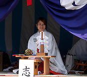 A Shinto priestess makes offerings to individual people who offer some coins.