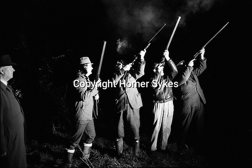 Wassailing the Apple Tree. Carhampton Somerset. England . 1972<br /> <br /> The original use of the word 'wassail' was as a greeting when drinking the health of a person, and derives from the Anglo-Saxon wes hal, or 'Be in good health'. Later it came to describe a custom observed on New Year's Eve and Twelfth Night of drinking healths from a wassail-bowl. Connected with this appears to have been the practice of wassailing cattle or fruit-trees to encourage<br /> them to thrive, a custom performed either right at the end of an old year or at the beginning of a new.  The people of Carhampton carry it out on the date of the old<br /> Twelfth Night (17 January) in an apple orchard behind the Butchers' Arms Inn. The wassailers gather round one of the largest apple trees to address it, sing the wassailing song, and fire guns into the tree to frighten off the evil spirits. After warm cider with toast in it has been passed around, the health of the tree is drunk, and toast put in the branches, supposedly for the birds who, it is hoped, will keep a watchful and benevolent eye on the tree for the following year.<br /> <br /> In 1972 the wassailing song went:<br /> Old apple tree we wassail thee and hoping thou wilt bear,<br /> For the Lord doth know where we shall be till apples come another year.<br /> To bear well and to bloom well so merry let us be,<br /> Let every man take off his hat and shout to the old apple tree.<br /> Old apple tree we wassail thee and hoping thou wilt bear<br /> Hatfuls capfuls three bushel barfuls,<br /> And a little heap under the stairs.<br /> Hip! Hip! Hooray!