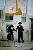 A younger Orthodox Jew gives his arm to a senior man for support during their walk through the streets of Mea Shearim, the section of Jerusalem where the ultra-orthodox Jews live. Jerusalem, Israel Mea Shearim.