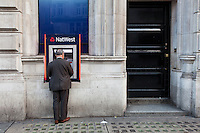 A man uses a cash machine (ATM) belonging to National Westminster Bank in a  street her Piccadilly Circus in London. UK Tuesday August 12th 2014