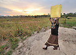 A young woman carries water as the sun rises in the Southern Sudanese village of Ligitolo. Families here are rebuilding their lives after returning from refuge in Uganda in 2006 following the 2005 Comprehensive Peace Agreement between the north and south.