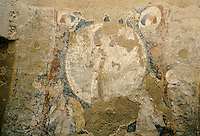 Fresco on the top head of the 34 meters Bamiyan Buddha. Hazarajat, Afghanistan..The parabolic niche in which this figure stands was once covered with paintings but most have fallen except for the heroic figure of the Sun God riding in his golden chariot pulled through a dark-blue sky by snow-white horses, which can still be seen on the soffit of the niche..The scene conceptualizes the relationship between the cosmos and the Buddha who is represented below as the embodiment of a Cosmic Buddha evolving from the sun in order to illuminate the world with total understanding. The iconography is syncretic, combining symbolism from Greece (Helios), Sasanian Persia (Mithra) and India (Surya). The Sun God is dressed in a long Sasanian cloak with a sword attached to the belt and he carries a scepter. This central figure is framed in a dark-red saw-toothed nimbus and the chariot with its riders bursts through the clouds. Above the nimbus there are flying geese and two truncated busts of women wearing pointed caps and holding billowing scarves over their heads. They represent the breezes which rise at sunrise and sunset. On either side of the Sun God there are two half-bird, half-human sirens, representing the deities who direct celestial music. Below them there are two winged female figures wearing helmets, each holding a shield and a spear. These may be seen as Night and Dawn, Mithras handmaidens, as Nike Athene, or as the wives of Surya.