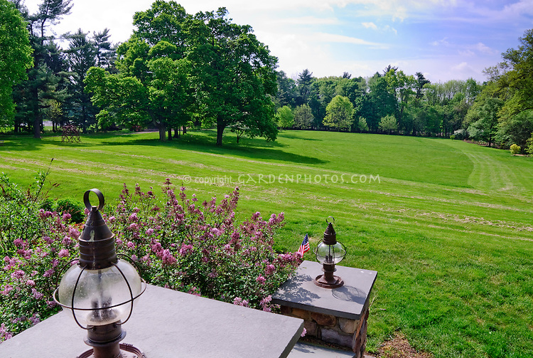 Fordhook Farm lawn and grounds historic estate open for tours, Warminster, PA, with Syringa lilac, steps with lighting lanterns, blue sky, trees