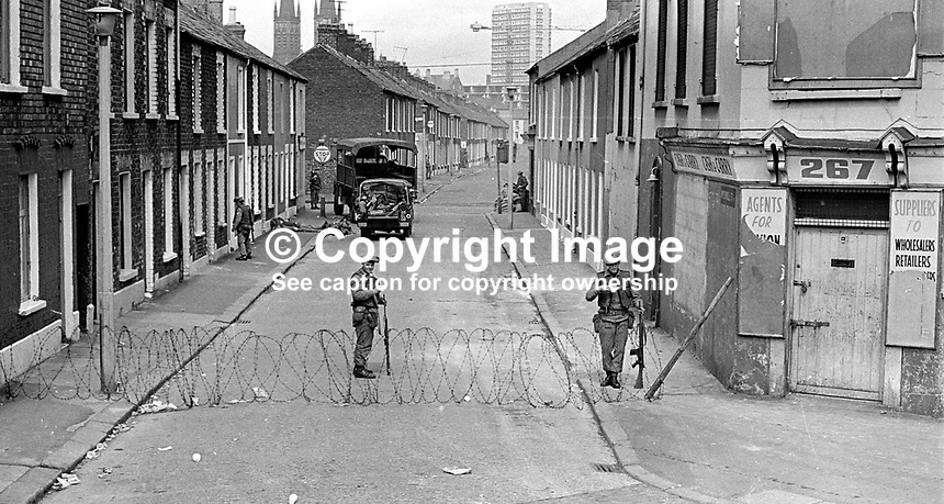 Soldiers on duty in the civilian-free streets during the curfew. 197007030251g. The British Army imposed during July 3 & 4, 1970, a 34 hour curfew (except for a two hour break to allow shopping) in approximately 50 streets in the Lower Falls district of Belfast, N Ireland, UK. A military helicopter hovered overhead warning people they would be arrested if they remained on the streets. An army search during the curfew uncovered 100 firearms, 100 home-made bombs, 250 lbs of explosives, 21000 rounds of ammunition and 8 two-way radios. This curfew is often seen as a turning point in souring relations between the Roman Catholic working class and the British Army. The army was no longer seen as the protector of the Catholic community...Copyright Image from Victor Patterson, 54 Dorchester Park, Belfast, UK, BT9 6RJ..Tel: +44 28 9066 1296.Mob: +44 7802 353836.Voicemail +44 20 8816 7153.Skype: victorpattersonbelfast.Email: victorpatterson@mac.com.Email: victorpatterson@ireland.com (back-up)..IMPORTANT: If you wish to use this image or any other of my images please go to www.victorpatterson.com and click on the Terms & Conditions. Then contact me by email or phone with the reference number(s) of the image(s) concerned.