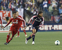 New England Revolution midfielder Juan Carlos Toja (7) dribbles as Toronto FC forward Luis Silva (11) defends. In a Major League Soccer (MLS) match, the New England Revolution (blue) defeated Toronto FC (red), 2-0, at Gillette Stadium on May 25, 2013.