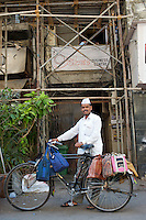 A lunch delivery man in Fort, Bombay. Commonly known as a Dabba-Wallah--he is one of thousands of others who are responsible for the distribution of 200,000 lunch boxes daily, monsoon or shine, with an error rate of 1 in 6 million--You can see the luch box sacks covering steel lunch containers hung along his bicycle - Bombay/Mumbai - India
