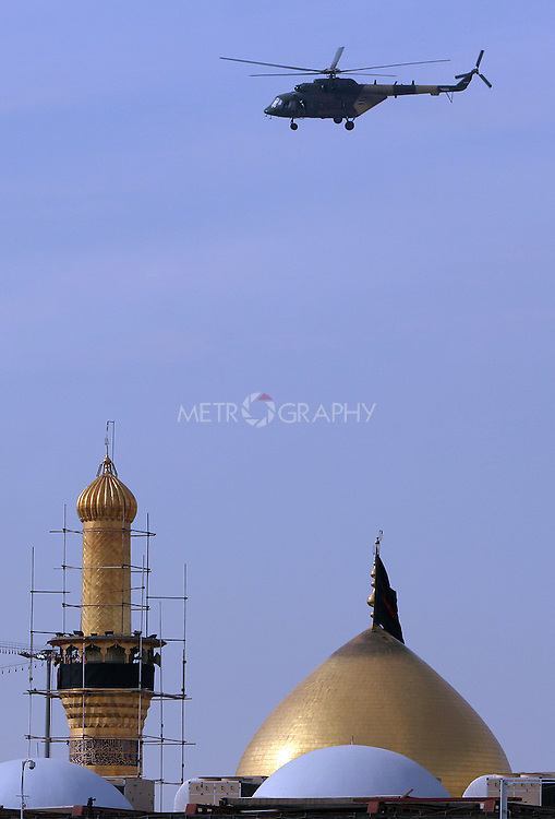 KARBALA, IRAQ: A helicopter circles over the city of Karbala on the last day of the Ashura festival...Shia pilgrims pray during the last day of the Ashura festival...Photo by Metrography