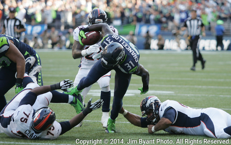 Seattle Seahawks Kam Chancellor (31) is tripped up by Denver Broncos center Manny Ramirez (66)  and tackle Chris Clark (75) after returning an interception back 52 yards in the fourth quarter at CenturyLink Field in Seattle, Washington on September 21, 2014. The Seahawks won 26-20 in overtime.