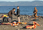 While another son waits nearby, a refugee mother helps her son change into dry clothing after disembarking on a beach near Molyvos, on the Greek island of Lesbos, on November 3, 2015. They arrived on a boat full of refugees from Turkey. They were received by local and international volunteers, then proceeded on their way toward western Europe. The boat was provided by Turkish traffickers to whom the refugees paid huge sums to arrive in Greece.